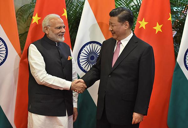 握手を交わすモディ首相と習近平国家主席(4月27日、中国湖北省武漢)