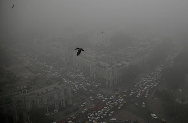 大気汚染によるスモッグの中を走るたくさんの自動車(2016年11月5日、ニューデリーのコンノート・プレイス=Photograph by Altaf Qadri, AP=)